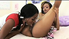 Ebony cutie gets wet while drilling her girlfriend with a strap-on