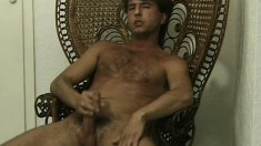 Gracious dude with hairy chest sits on wooden chair and masturbates